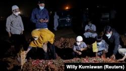 Seorang perempuan dan anak-anaknya saat pemakaman suaminya yang meninggal akibat COVID-19 di Bekasi, 27 Juli 2021. (Foto: Willy Kurniawan/Reuters)