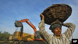 A laborer carries a basket filled with coal at a railway yard in the northern Indian city of Chandigarh, India, January 2011. (file photo)