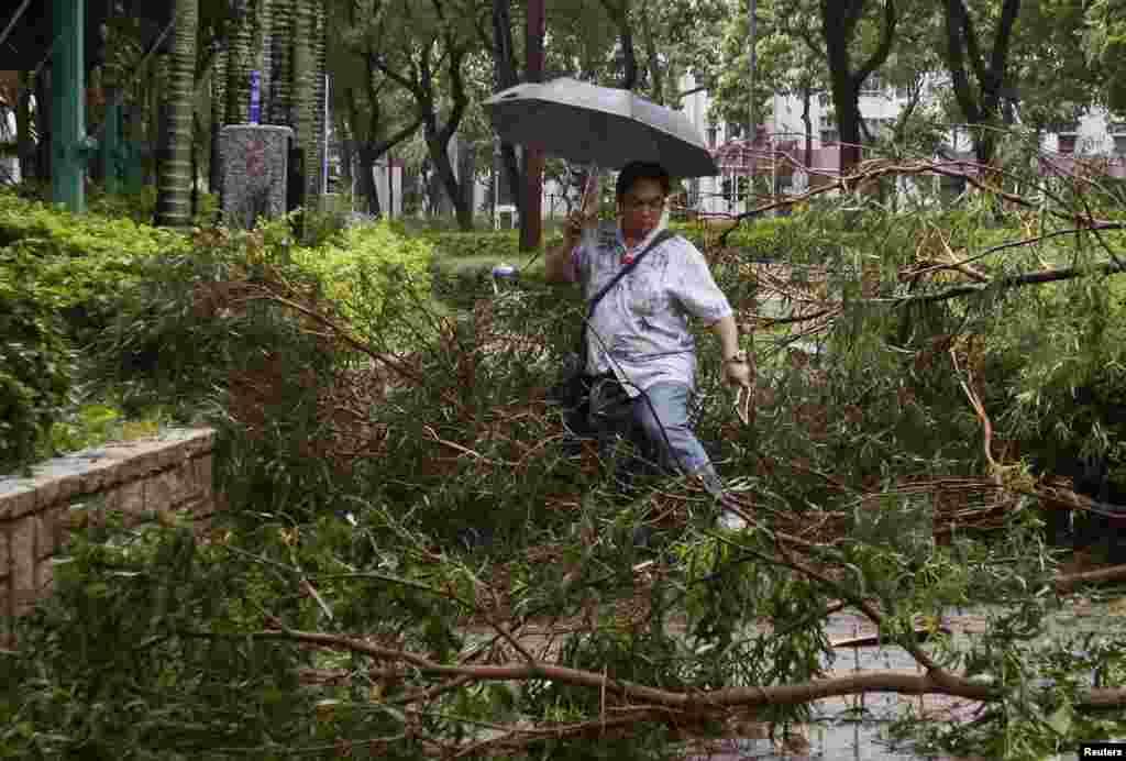 Seorang pria berjalan di antara ranting-ranting pohon yang jatuh dan memenuhi jalanan di Hong Kong akibat Topan Usagi (23/9). (Reuters/Bobby Yip)