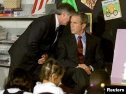 FILE - U.S. President George W. Bush listens as White House Chief of Staff Andrew Card informs him of a second plane hitting the World Trade Center, while Bush was at the Emma E. Booker Elementary School in Sarasota, Florida, Sept. 11, 2001.