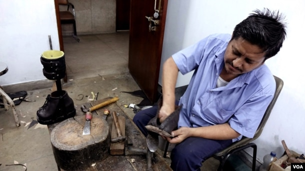 A worker is designing special shoes for leprosy patients at the Leprosy Mission Trust India hospital, Kolkata, Sept. 20 2016. (M. Hussain/VOA)