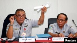 Tatang Kurniadi, left, chief of the National Transportation Safety Committee (NTSC), holds a model plane during a news conference in Jakarta, Jan. 29, 2015.