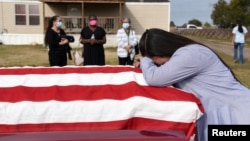 Lila Blanks holds the casket of her husband, Gregory Blanks, 50, who died of the coronavirus disease (COVID-19), ahead of his funeral in San Felipe, Texas, U.S., January 26, 2021.