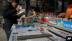 Un hombre arregla revistas cerca de periódicos con titulares sobre los reclamos de China contra EE.UU. por la detención de la jefe financiera de Huawei, Meng Wanzhou. Beijing, diciembre 10 de 2018.