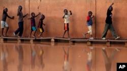 Des enfants traversent les eaux de crues sur des planches à Niamey, Niger, 2 août 2009.