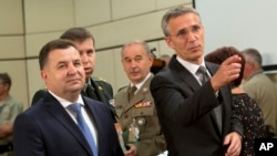 NATO Secretary-General Jens Stoltenberg, right, and Ukraine's Defense Minister Stepan Poltorak, left, arrive for a meeting of the NATO-Ukraine Commission at NATO headquarters in Brussels, June 25, 2015.