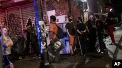 People watch as police arrest protesters for breaking a curfew during a solidarity rally calling for justice over the death of George Floyd, Friday, June 5, 2020, in the Brooklyn borough of New York. Floyd, an African American man, died on May 25…