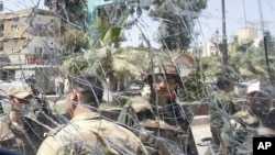 Syrian army soldiers, are seen through a damaged military truck window which was attacked by a roadside bomb, in Daraa city, southern Syria. The explosion targeted the Syrian military truck just seconds after a team of U.N. observers passed by.