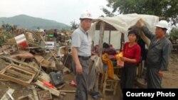 북한 적십자 소속 재난대응요원들이 지난 8월말 함경북도 회령시 주변 홍수 피해 지역에서 피해 규모를 파악하고 있다. 국제적십자가 지난달 공개한 북한 수해 보고서에 들어있는 사진이다.