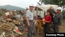 북한 적십자 소속 재난대응요원들이 지난 8월 말 함경북도 회령시 주변 홍수 피해 지역에서 피해 규모를 파악하고 있다. 국제적십자가 20일 공개한 북한 수해 보고서에 들어있는 사진이다.