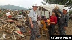 북한 적십자 소속 재난대응요원들이 지난 8월말 함경북도 회령시 주변 홍수 피해 지역에서 피해 규모를 파악하고 있다. 국제적십자가 20일 공개한 북한 수해 보고서에 들어있는 사진이다.