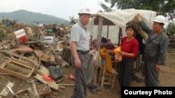 북한 적십자 소속 재난대응요원들이 지난 8월말 함경북도 회령시 주변 홍수 피해 지역에서 피해 규모를 파악하고 있다. 국제적십자가 지난 9월 공개한 북한 수해 보고서에 들어있는 사진.