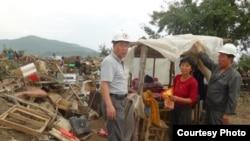 북한 적십자 소속 재난대응요원들이 지난 8월 말 함경북도 회령시 주변 홍수 피해 지역에서 피해 규모를 파악하고 있다. 국제적십자가 지난달 20일 공개한 북한 수해 보고서에 들어있는 사진.