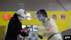 신종 코로나바이러스가 처음으로 발병한 중국 우한의 고속버스터미널에서 30일 안면가리개를 쓴 역무원(오른쪽)이 승객과 대화하고 있다.