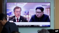 FILE - People watch a TV screen showing file footage of South Korean President Moon Jae-in and North Korean leader Kim Jong Un during a news program ahead of the inter-Korean summit at the Seoul Railway Station in Seoul, South Korea, April 26, 2018.