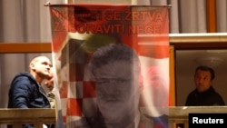 "Bosnian Croats hang a flag displaying a portrait of General Slobodan Praljak and a message that reads, ""Your sacrifice will never be forgotten,"" as people pray and light candles for the convicted general, who killed himself seconds after a judge at a U.N. tribunal confirmed his sentence for war crimes, in Mostar, Bosnia-Herzegovina, Nov. 29, 2017."