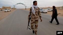 Dân quân thuộc lực lượng thân Gadhafi canh gác tại một chốt kiểm soát ở Bin Jawad