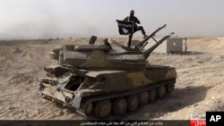 FILE - An Islamic State militant displays the group's flag from a tank captured from Syrian government forces in al-Qaryatayn, a central Syrian town southwest of Palmyra.