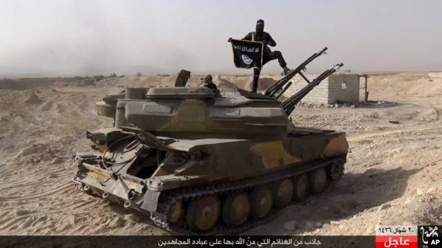 Một chiến binh Hồi giáo Nhà nước giơ lá cờ của nhóm khi đứng trên một chiếc xe tăng của lực lượng chính phủ Syria bị nhóm này bắt tại thị trấn al-Qaryatayn phía tây nam Palmyra, miền trung Syria.
