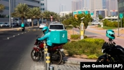 A delivery driver for the app Deliveroo prepares to make a delivery, in Dubai, United Arab Emirates, Thursday, Sept. 9, 2021. (AP Photo/Jon Gambrell)