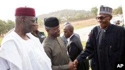 Muhammadu Buhari (à droite) accueilli par son vice-président Yemi Osinbajo (au centre) à son retour à Abuja, après une absence d'un mois et demi, le 10 mars 2017.