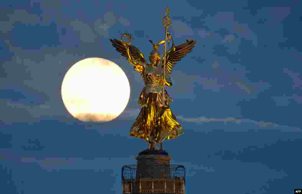 The full moon behind the victory column in Berlin, Germany