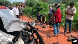 In this photo provided by Cambodia National Police, onlookers stand around the mangled wreckage of Cambodia's Prince Norodom Ranariddh's car after a collision with another vehicle outside Sihanoukville, Cambodia, Sunday, June 17, 2018. Ranariddh has been seriously injured in the road crash that killed his wife and injured at least seven other people early Sunday. (Cambodia National Police via AP)
