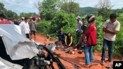 In this photo provided by Cambodia National Police, onlookers stand around the mangled wreckage of Cambodia's Prince Norodom Ranariddh's car after a collision with another vehicle outside Sihanoukville, Cambodia, Sunday, June 17, 2018.