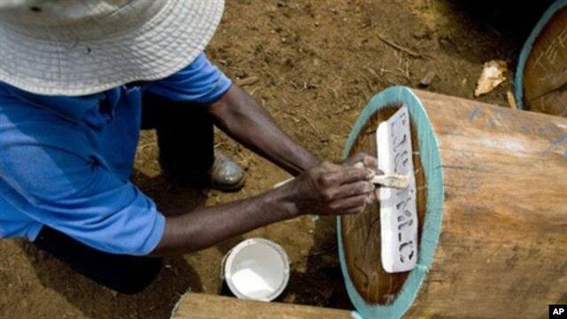 An employee of the Swiss monitoring company SGS registers a tree trunk near Buchanan, Liberia, 26 Feb 2010