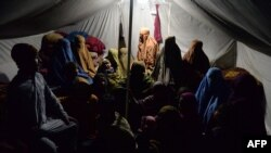 جلال آباد (افغانستان) کے ایک پناہ گزین کیمپ کے ایک حیمے میںں بے گھر عورتیں اپنے بچوں کے ساتھ۔ 18 جنوری 2017