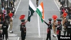 واہگہ بارڈر پر سکیورٹی اہلکار پاکستانی اور بھارتی پرچموں کے ساتھ