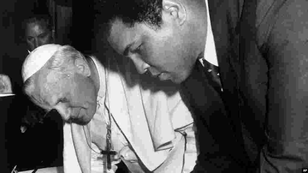 Jean-Paul II et l'ancien champion de boxe poids lourd Mohamed Ali, signe des documents, à Vatican, le 6 juin 1982.
