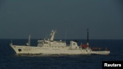 A Chinese marine surveillance ship cruises in waters about 28 km (17 miles) northwest of one of the disputed islands called Senkaku in Japan and Diaoyu in China, in the East China Sea, in this handout photo released by Japan Coast Guard's 11th Regional Co