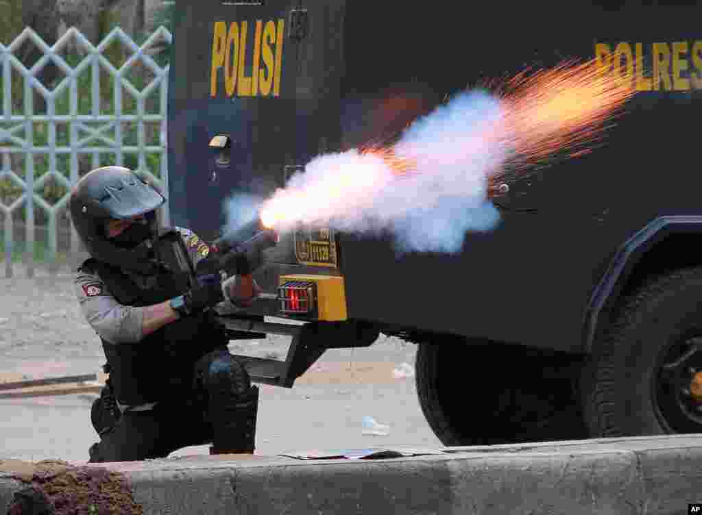 An Indonesian police officer fires his tear gas launcher at protesters during a rally against the fuel price increases in Makassar, Indonesia.