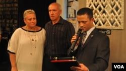 Михаил Белогородский вручает памятную награду Татьяне и Леониду Тимошенко. Их сын-полицейский был убит при исполнении служебных обязанностей.