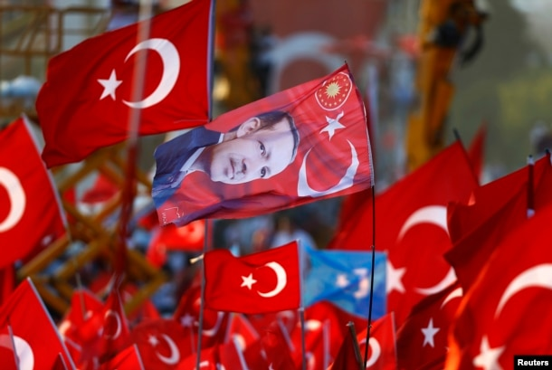 FILE - A flag with the picture of Turkey's President Tayyip Erdogan is featured during the Democracy and Martyrs Rally, organized by Erdogan and the ruling AK Party in Istanbul, Aug. 7, 2016.