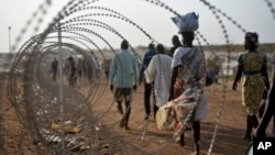 A file photo taken Jan. 19, 2016 shows displaced people next to a razor wire fence at the United Nations base in the capital Juba, South Sudan.