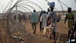 Para pengungsi berjalan di sepanjang pagar kawat berduri dekat markas PBB di ibukota Juba, Sudan Selatan (Foto: dok).