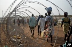 FILE - Displaced people walk next to a razor wire fence at the United Nations base in the capital Juba, South Sudan, Jan. 19, 2016.
