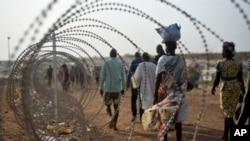 FILE - Displaced people walking next to a razor wire fence at the United Nations base in the capital Juba, South Sudan.