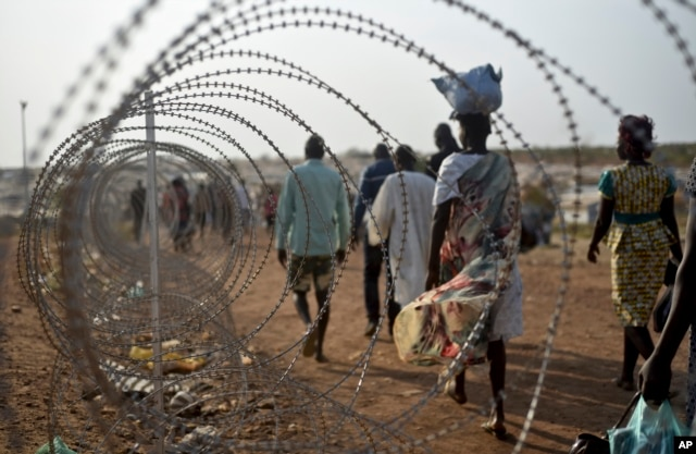 FILE - This photo taken Jan. 19, 2016 shows displaced people walking next to a razor wire fence at the United Nations base in the capital Juba, South Sudan.