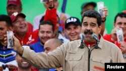 FILE - Venezuela's President Nicolas Maduro holds up a mock 100-bolivar bill depicting the president of the National Assembly Henry Ramos Allup, during a pro-government rally in Caracas, Venezuela, Dec. 17, 2016.