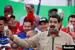FILE - Venezuela's President Nicolas Maduro holds up a mock 100-bolivar bill depicting the president of the National Assembly Henry Ramos Allup, during a pro-government rally in Caracas, Dec. 17, 2016.