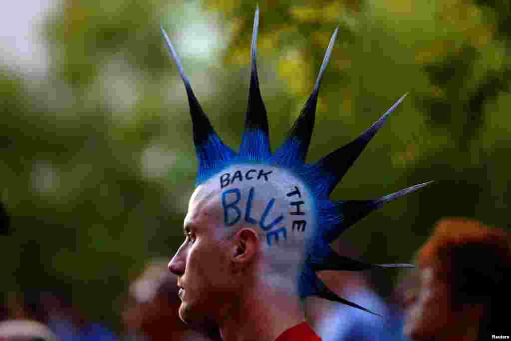 បុរសម្នាក់ដែលមានម៉ូដសក់របស់ក្រុមកុលសម្ព័ន្ធ Mohawk ដែលមានសរសេរពាក្យថា «Back The Blue» ចូលរួមពិធីដុតភ្លើងទៀនមួយនៅសាលាក្រុង Dallas ដើម្បីចងចាំដល់មន្រ្តីប៉ូលិសដែលត្រូវបានគេសម្លាប់កាលពីសប្តាហ៍មុន នៅក្នុងក្រុង Dallas រដ្ឋ Texas កាលពីថ្ងៃទី១១ ខែកក្កដា ឆ្នាំ២០១៦។