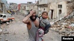 Seorang pria menangis saat ia membawa putrinya dan berjalan dari bagian yang dikuasai Islamic State di Mosul menuju ke arah pasukan khusus Irak selama pertempuran di Mosul, Irak, 4 Maret 2017 (foto: REUTERS/Goran Tomasevic)