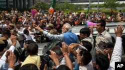 Opposition Bharatiya Janata Party (BJP) leader and India's next prime minister Narendra Modi greets the crowd standing on the footboard of his SUV outside the New Delhi airport, India, May 17, 2014.