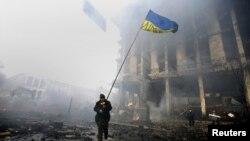 Demonstrant drži ukrajinsku zastavu napredujući kroz zapaljene barikade na Trgu nezavisnosti u Kijevu, 20. februara 2014.