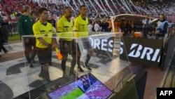L'arbitre brésilien Wilton Pereira Sampaio (C) et ses assistants passent devant un écran de l'assistance vidéo à l'arbitrage(VAR) avant le début de la demi-finale de la Copa Libertadores 2017 au stade Monumental de Buenos Aires, le 25 octobre 2017.