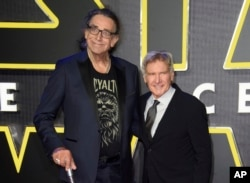 FILE - This December 16, 2015 file photo shows Peter Mayhew, left, and Harrison Ford at the European premiere of the film 'Star Wars: The Force Awakens ' in London.