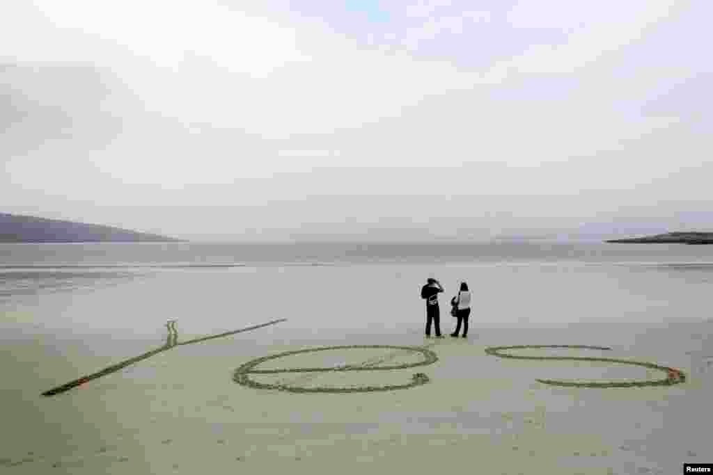 "The word ""Yes"" is written in sand as people look out over the bay at Luskentyre beach on the Isle of Harris in the Outer Hebrides, Scotland. The referendum on Scottish independence will take place on Sept. 18, when the country will vote whether or not to end the 307-year-old union with the rest of the United Kingdom."